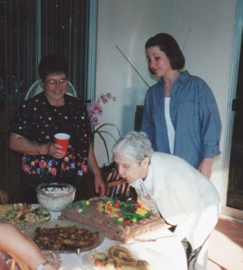 My mother blowing out the candles on her cake with my daughter looking on